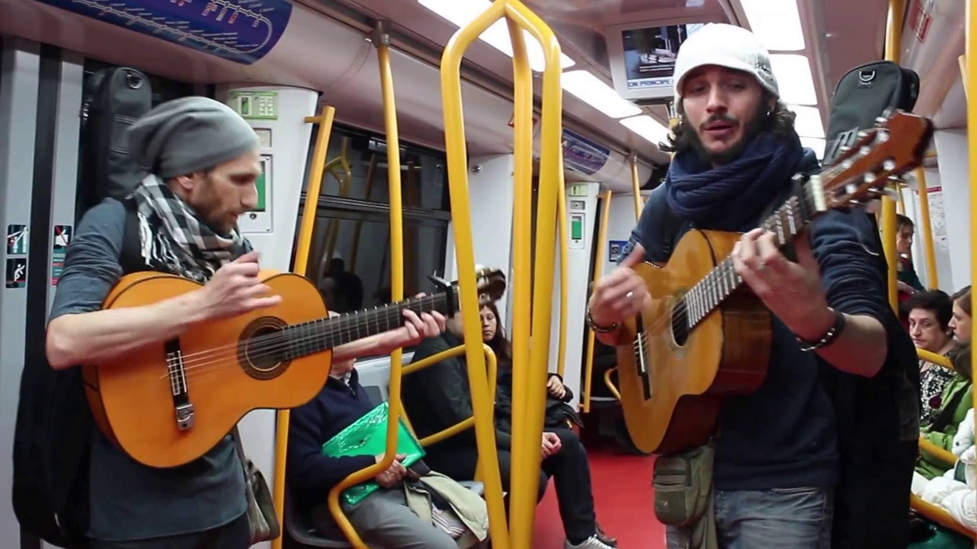 Cantantes con una guitarra española en el metro
