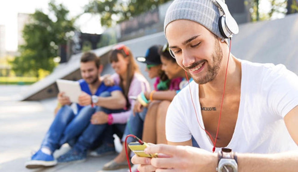 Chico joven escuchando una canción desde su móvil.